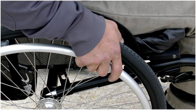 man gripping wheel chair